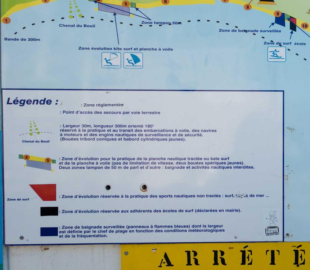 Sign board at a French beach. Map with legend showing lifeguard and watersports areas.