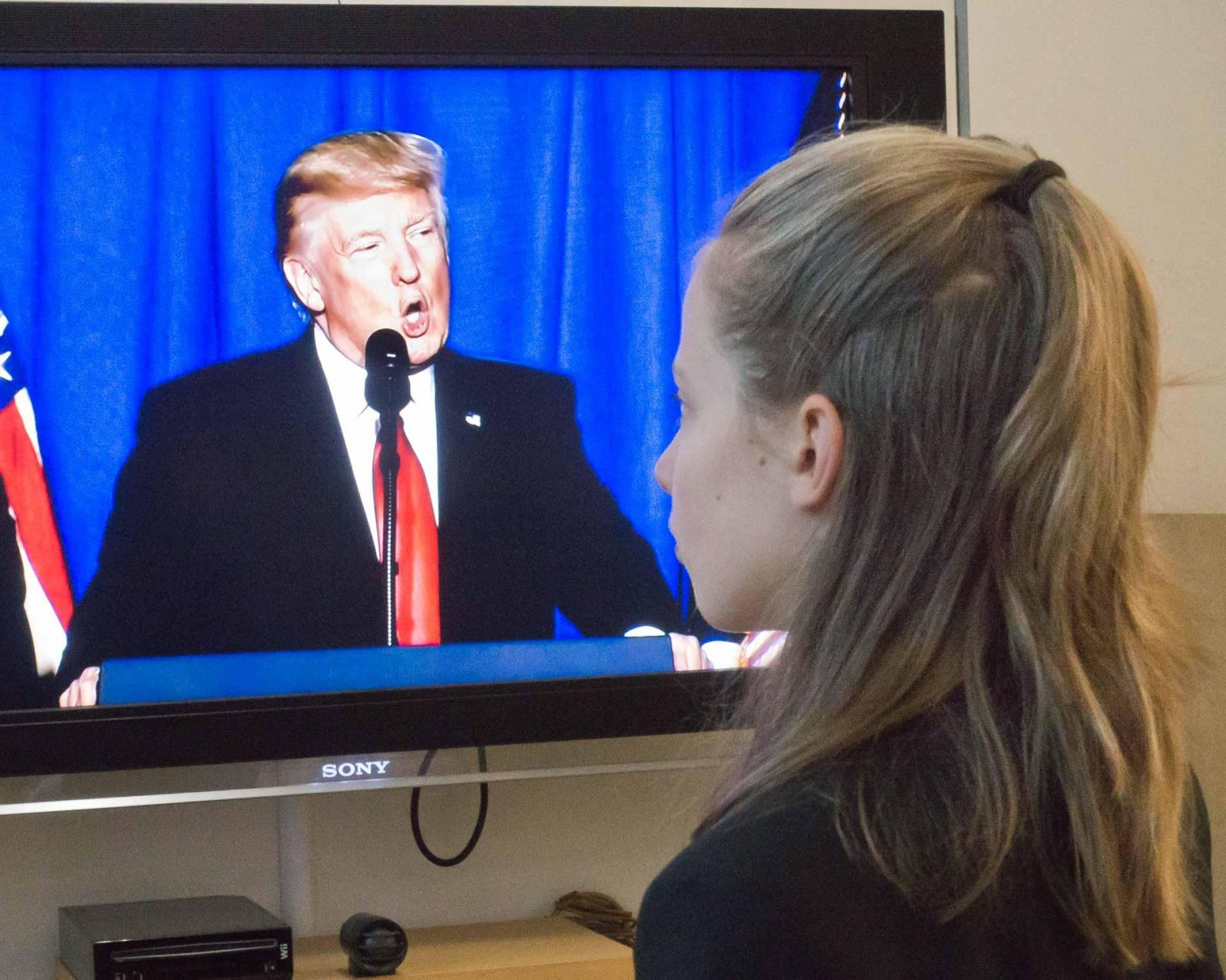 Talk to your older kids about the news - here's why on Falcondale Life blog. Girl watches Trump on TV