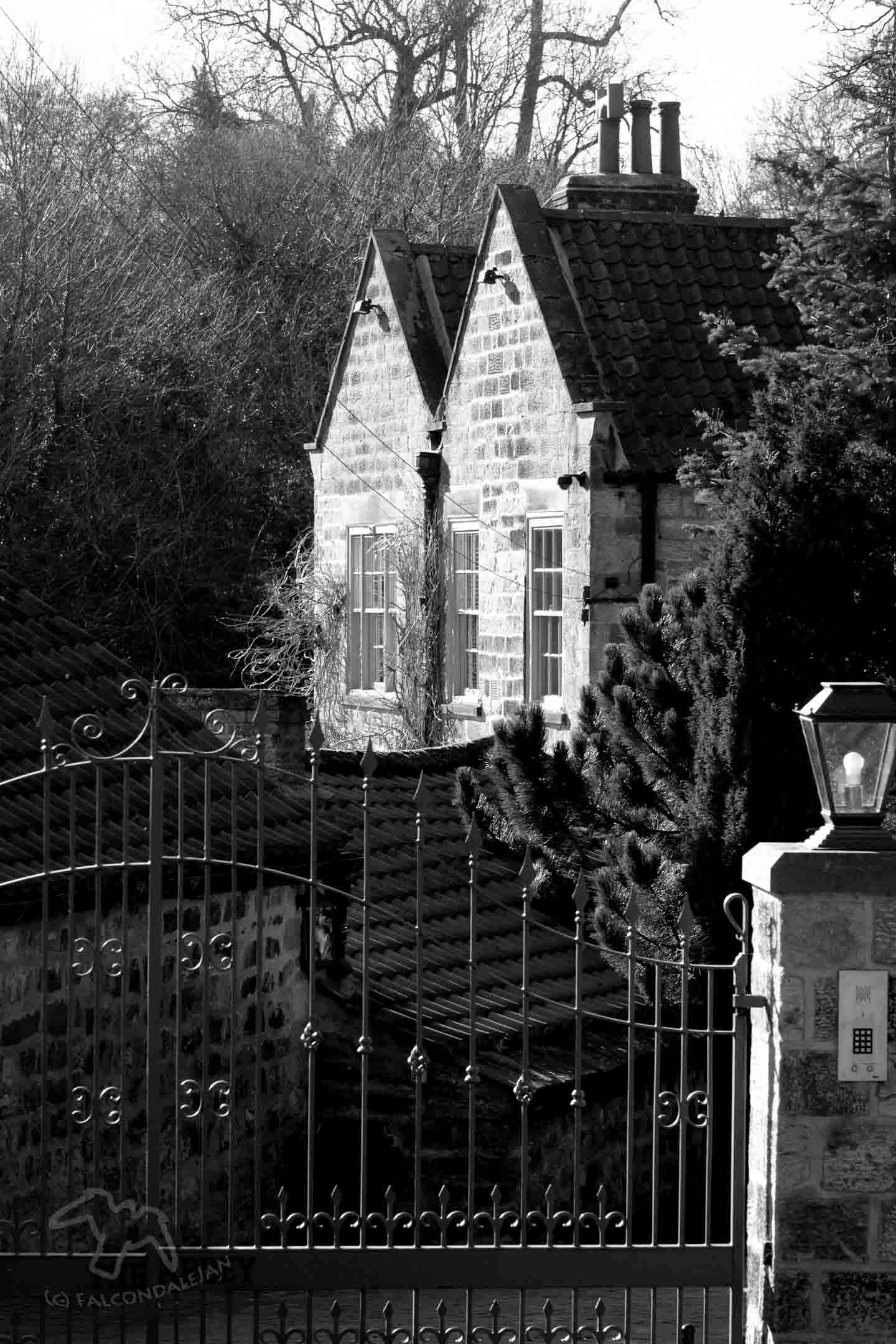Gabled stone house behind iron gate monochrome Reasons to shoot black and White part 2: Flatten Perspective on Falcondale Life blog. In this short series I look at some reasons I've chosen to turn a photo monochrome.
