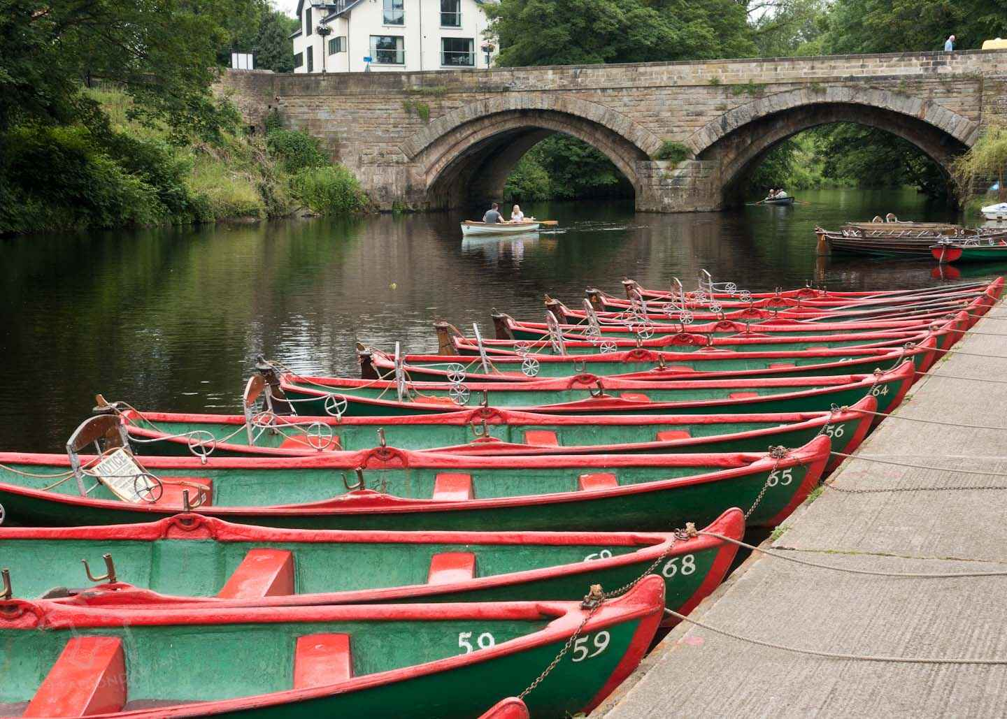 Visitor information for the river Nidd at Knaresborough Waterside in North Yorkshire. See the rowing boats and use these repeating pattern photo composition tips. Visit Knaresborough Waterside and try Repeating Pattern Photo Composition on Falcondale Life blog. Image description: a line of rowing boats moored on the Nidd near High Bridge.