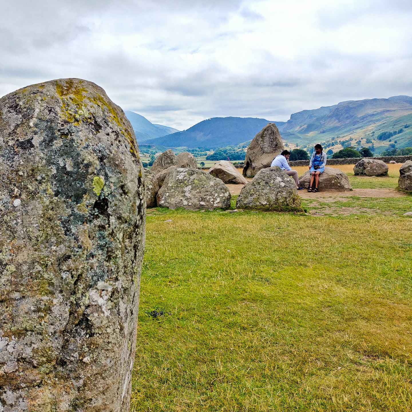 I only had my phone and 15 minutes, so how did I get some nice photos of Castlerigg Stone Circle in the Lake District? Photography tips and visitor info. Taking photos at Castlerigg Stone Circle in the Lake District on Falcondale Life blog. Image description: part of Castlerigg Stone Circle with visitors.