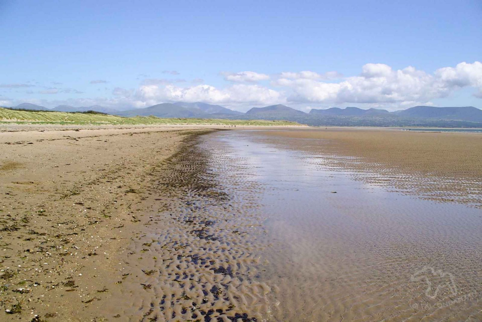 Ideas and tips for a vacation that's suitable for sensitive people. Where could we take an anxious teenager or child on holiday? Plan calmer family travel. Image description: large empty beach with blue sky and ripples.