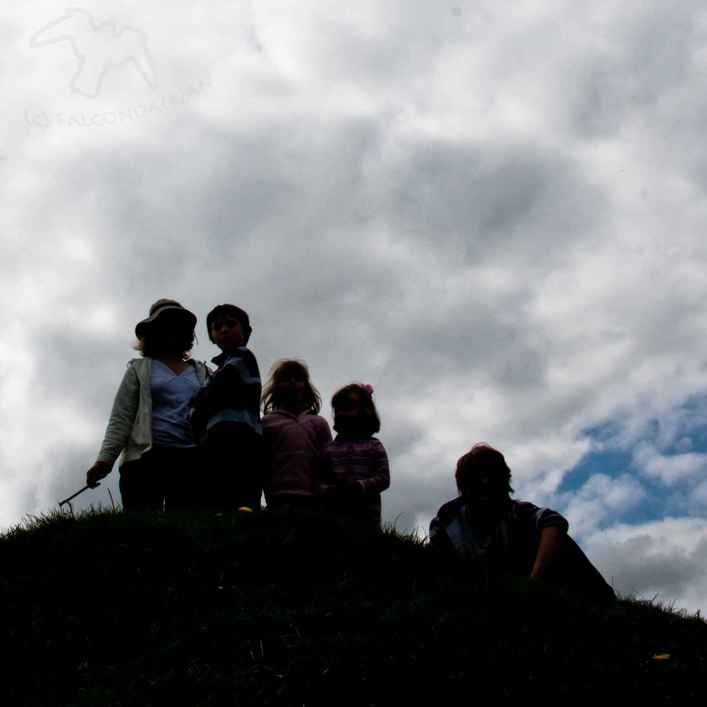 Ideas and tips for a vacation that's suitable for sensitive people. Where could we take an anxious teenager or child on holiday? Plan calmer family travel. Image description: Silhouette of large family group on a hill with clouds.
