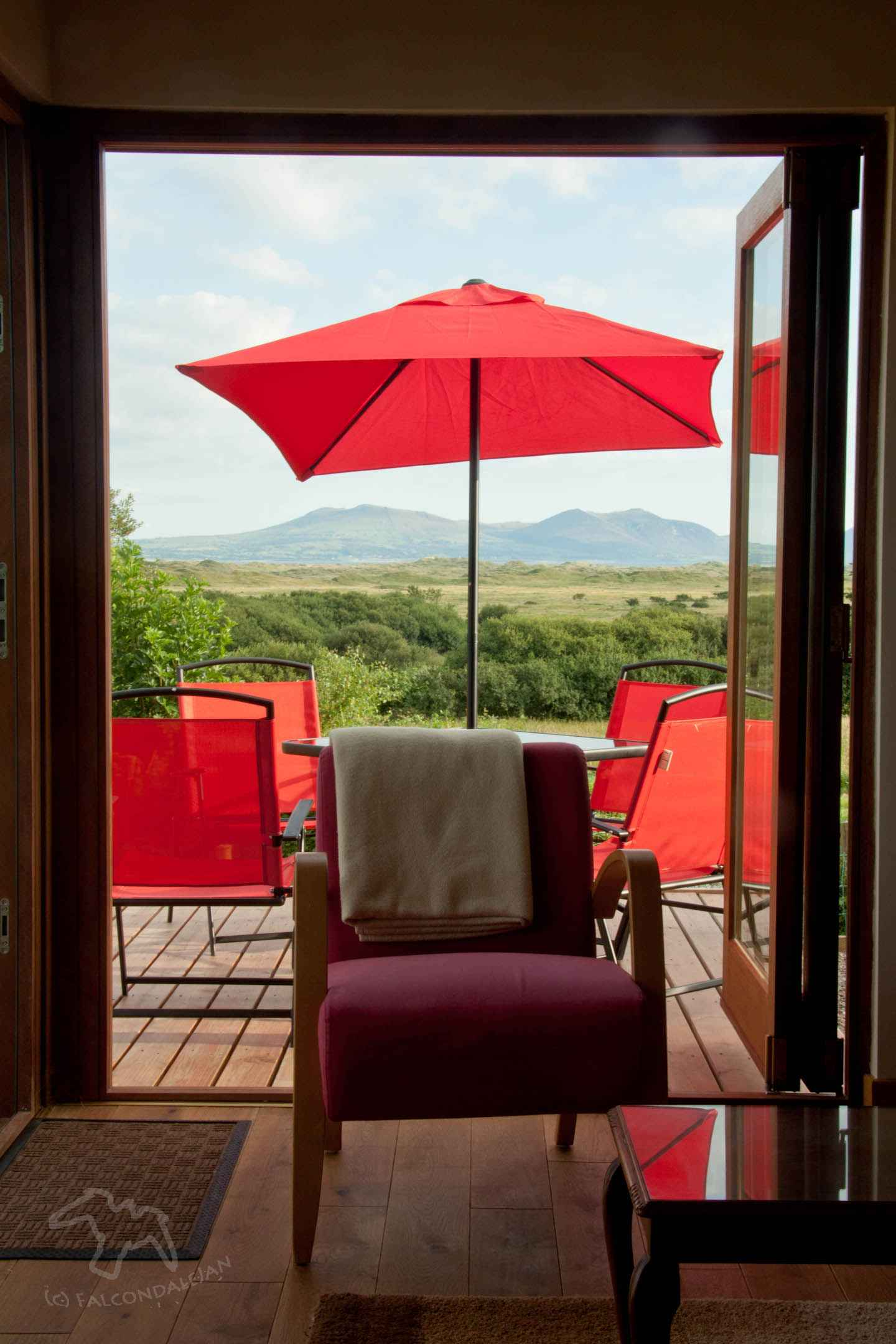 Ideas and tips for a vacation that's suitable for sensitive people. Where could we take an anxious teenager or child on holiday? Plan calmer family travel. Image description: view out of open patio doors, red furniture, mountains beyond.