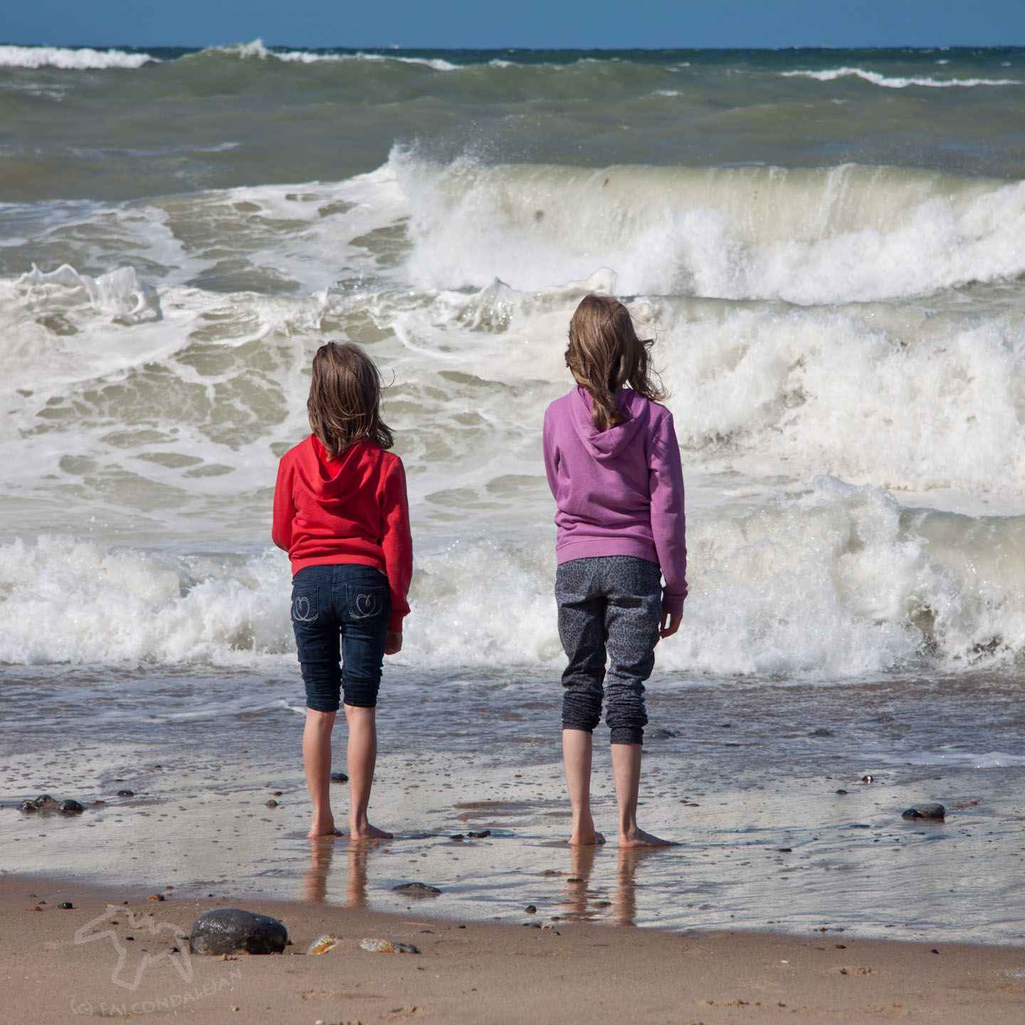 Ideas and tips for a vacation that's suitable for sensitive people. Where could we take an anxious teenager or child on holiday? Plan calmer family travel. Image description: 2 girls in hoodies and rolled-up trousers stare out at waves on the sea.