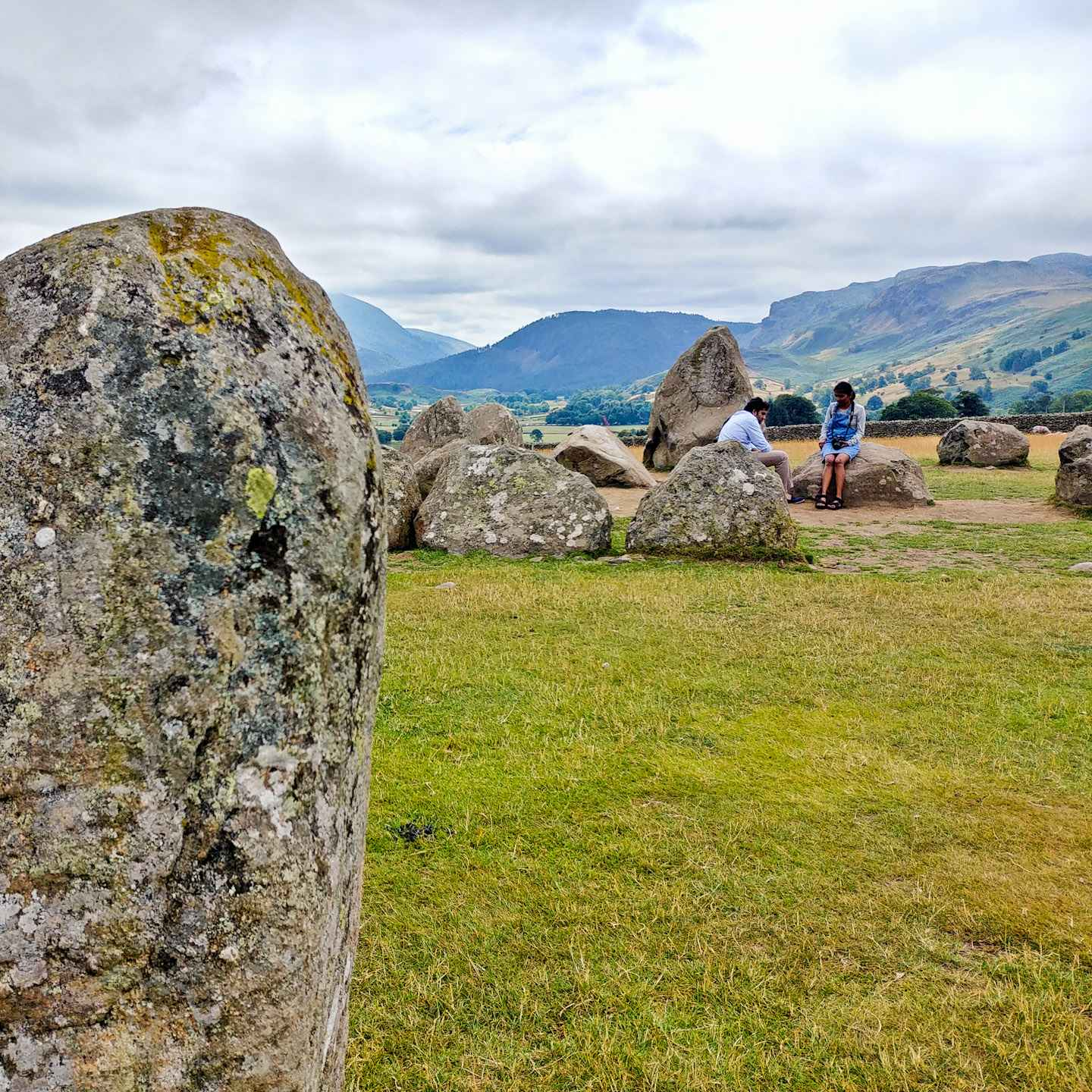 I only had my phone and 15 minutes, so how did I get some nice photos of Castlerigg Stone Circle in the Lake District? Photography tips and visitor info. Taking photos at Castlerigg Stone Circle in the Lake District on Falcondale Life blog. Image description: high contrast image of part of Castlerigg Stone Circle, the landscape beyond and tourists