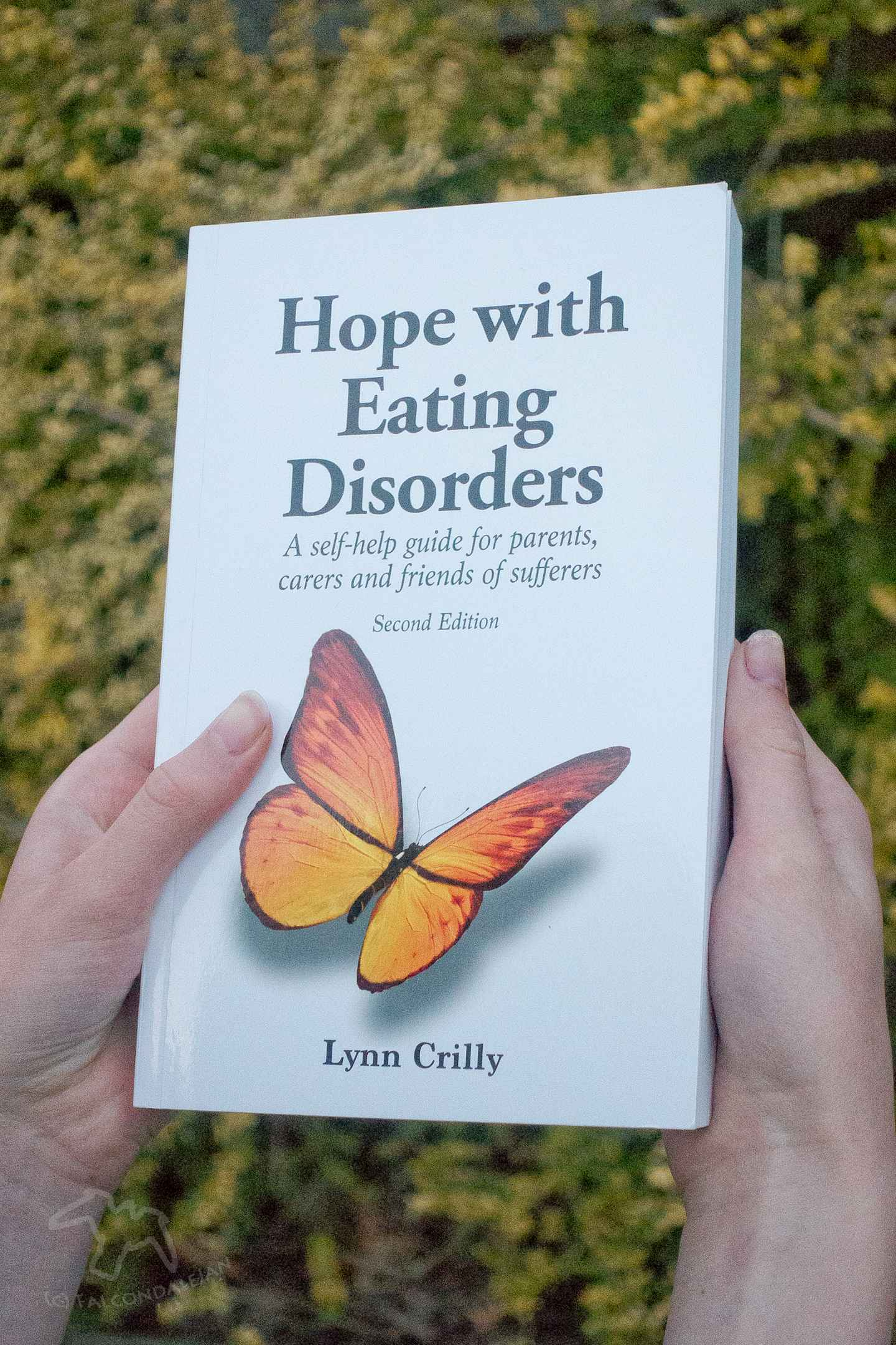 """An in depth review of Lynn Crilly's book """"Hope with Eating Disorders"""" by the parent and carer of an ED sufferer. A practical book on these mental illnesses. Hope with Eating Disorders book review on Falcondale Life blog. Image description: hands holding the book, Hope with Eating Disorders by Lynn Crilly"""