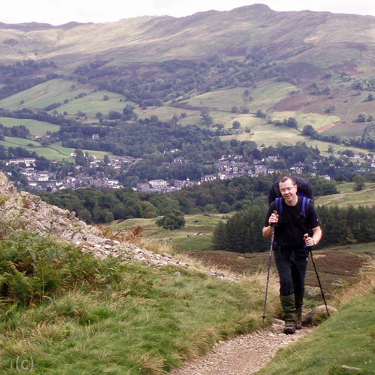A review of walking poles for hiking with arthritis or joint pain. How to use walking poles and how could walking poles help on a trek or ramble. On Falcondale Life blog. Image description: man with toddler in back carrier using a pair of walking poles.