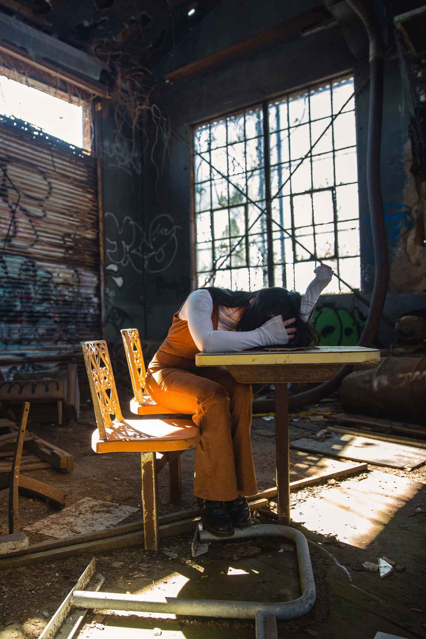 """An in depth review of Lynn Crilly's book """"Hope with Eating Disorders"""" by the parent and carer of an ED sufferer. A practical book on these mental illnesses. Hope with Eating Disorders book review on Falcondale Life blog. Image description: A girl hides her face in her arms, sitting at a dining table in a tatty old room."""